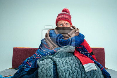 Sticker Bearded sick man with flue sitting on sofa at home or studio covered with knitted warm clothes. Illness, influenza, pain concept. Relaxation at Home. Healthcare Concepts.