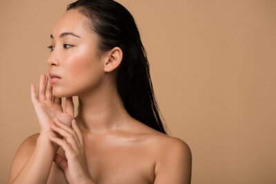 Sticker beautiful naked asian girl  looking away and touching face isolated on beige