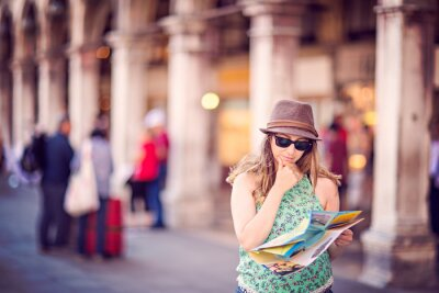 Beautiful tourist woman is confused about finding directions. She is holding a map and hand on the chin.