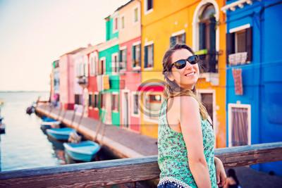 Beautiful tourist woman is posing on the bridge of Burano island of Venice, italy