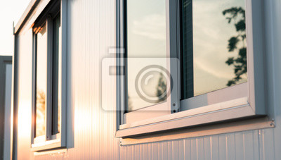 Sticker beautiful warm sunrise light shining on house glass window with town nature reflection in the morning, modern home exterior view