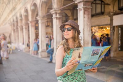 Beautiful woman tourist is looking around and holding a map.