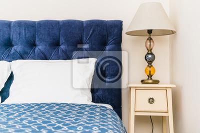 Blaues bett mit weichem kopfteil und nachttisch mit lampe notebook ...