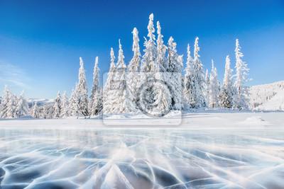 Sticker Blaues Eis und Risse auf der Oberfläche des Eises. Gefrorener See unter einem blauen Himmel im Winter. Die Hügel von Pinien. Winter. Karpaten, Ukraine, Europa