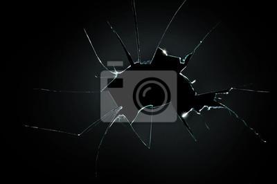 Sticker broken cracked glass with big hole over black background