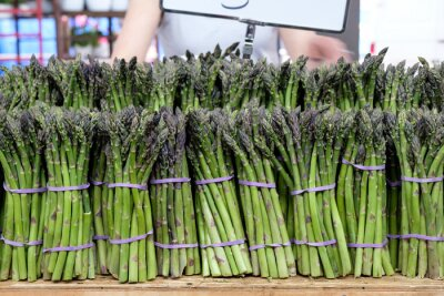 Sticker Bunches of asparagus bound with rubber bands for sales at summer market