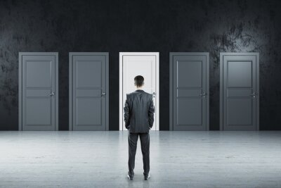 Businessman standing in gray room and looking on five closed doors