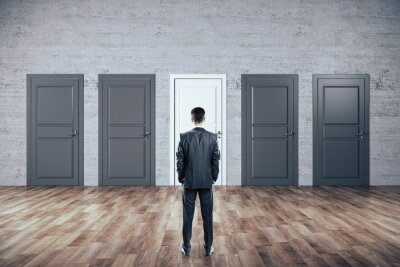 Businessman standing in room and looking on five closed doors
