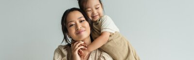 Sticker cheerful asian toddler daughter hugging happy mother isolated on gray, banner