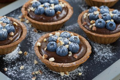 Sticker chocolate mousse with fresh blueberries and nuts in tartlets