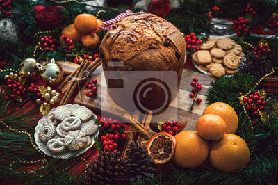 Sticker Christmas ingredients table with a Panettone in the center on a wooden board, accompanied by orange, cookies, cinnamon, pine. Festive pine decoration on red rustic background