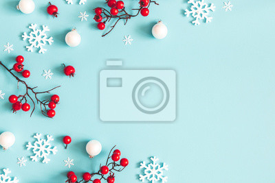 Sticker Christmas or winter composition. Snowflakes and red berries on blue background. Christmas, winter, new year concept. Flat lay, top view, copy space