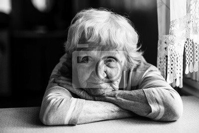 Sticker Close-up black and white portrait of a old woman at the table in home.