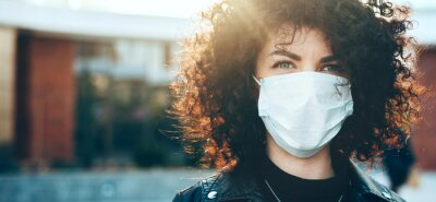 Sticker Close up portrait caucasian businesswoman with curly hair is looking at camera while wearing a protective mask