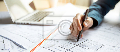 Sticker Close up woman hand working of Architect sketching project on blueprint at site construction work. Concept of architect, engineer in the office desk construction project banner