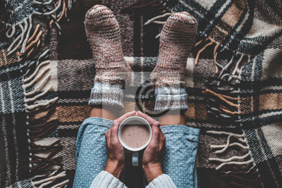 Sticker Cozy woman in knitted winter warm socks and in pajamas holding a cup of hot cocoa during resting on checkered plaid blanket at home in winter time. Cozy time and winter drinks. Top view