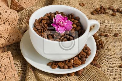 Cup mit Kaffeebohnen gefüllt und rosa Blume