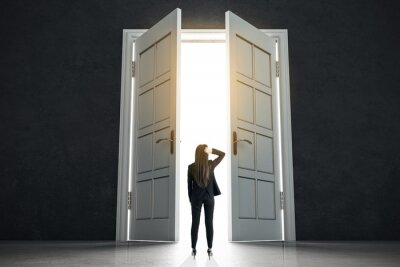 Decision making concept with businesswoman standing in front of white doors in abstract bright space.
