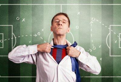 Der Büromann öffnet ein weißes Hemd und zeigt eine Fußballform. Vor dem Hintergrund des Coaching-Schemas des Spiels. Held