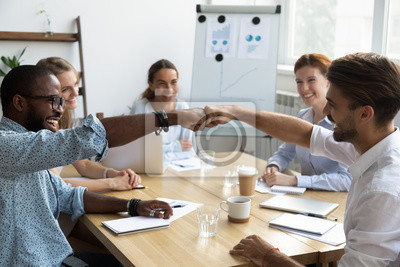 Sticker Diverse company staff girls guys sitting at desk in boardroom feel happy and satisfied celebrating success at work. Diverse colleagues fist bumping greeting each other express friendship and respect