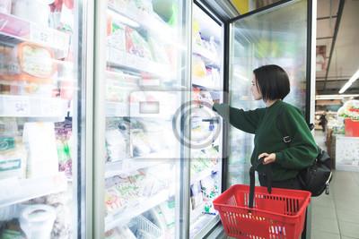 Sticker Ein Mädchen mit einem Korb nimmt Tiefkühlkost aus dem Kühlschrank des Supermarktes. Das Mädchen wählt Waren im Speicher. Einkaufen im Supermarkt.