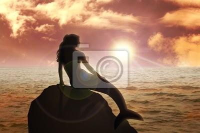 Eine Meerjungfrau sitzt auf dem Felsen bei Sonnenuntergang