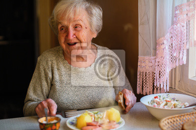 Sticker Elderly woman eat sitting at dinner table at home.