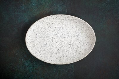 Sticker Empty oval plate on dark concrete background. Top view, with copy space