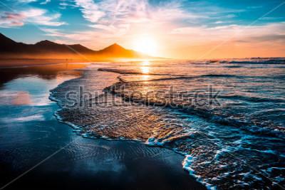 Sticker Erstaunlicher Strand-Sonnenuntergang mit endlosem Horizont und einsamen Figuren in der Ferne und unglaublichen Schaumwellen. Vulkanhügel im Hintergrund.