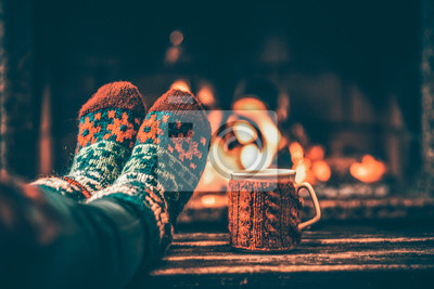 Sticker Feet in woollen socks by the Christmas fireplace. Woman relaxes by warm fire with a cup of hot drink and warming up her feet in woollen socks. Close up on feet. Winter and Christmas holidays concept.