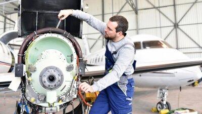 Sticker Flugzeugemechaniker repariert Triebwerk von Flugzeug im Hangar // Arbeiter reparieren Motor aus dem Flugzeug im Hangar