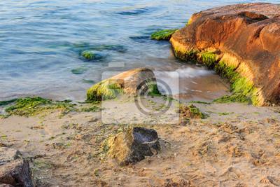 Flutwelle strugle mit Stein am Sandstrand