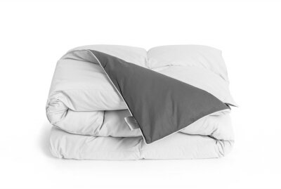 Sticker Folded soft white duvet, blanket or bedspread with the gray back side and empty white label, against white background. Close up photo