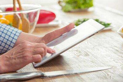Frau mit digitalen Tablette in der Küche