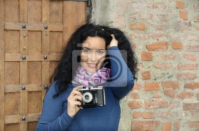 Frau mit Fotokamera auf Film, vor der Holztür