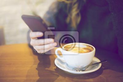 Frau SMS eine Nachricht im Café. Kaffee auf dem Tisch.
