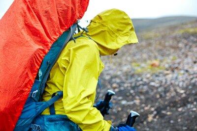 Frau Wanderer auf der Spur in der Insel Berge. Trek im Nationalpark Landmannalaugar, Island. Frau zu Fuß in den Regen mit einem Rucksack in einem Regenmantel und trägt eine wasserdichte Jacke