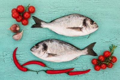 Sticker Frische Dorade Fisch mit Gemüse auf blauem Tisch. Textfreiraum, Draufsicht