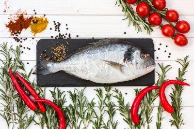 Sticker Frische Dorade Fisch, Rosmarin, Kirschtomaten, chilly Pfeffer auf weißem Holztisch. Draufsicht.
