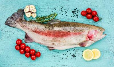 Sticker Frische Forelle Fisch mit Gemüse auf blauem Holztisch. Draufsicht