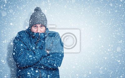 Sticker Frozen man in a blue jacket and hat stands against the wall, snow is falling around