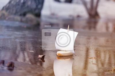 Frühling. Ein hölzernes Boot mit einem Segel schwimmt entlang einer Waldpfütze. Muskelaufbau. Draußen
