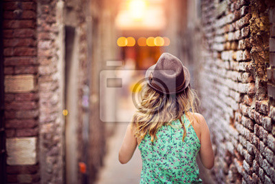 Girl with a hat walking and discovering places in narrow street.