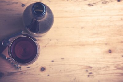 Glas Rotwein auf einem hölzernen Hintergrund