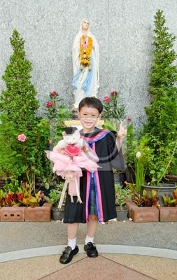 Grund Junge stolz trägt seine Graduierung Kleid