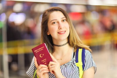 Happy beautiful woman exciting to travel. she showing her passport and ready to boarding.