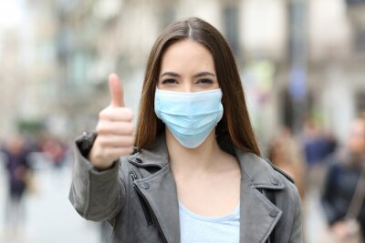 Sticker Happy woman with mask gesturing thumbs up