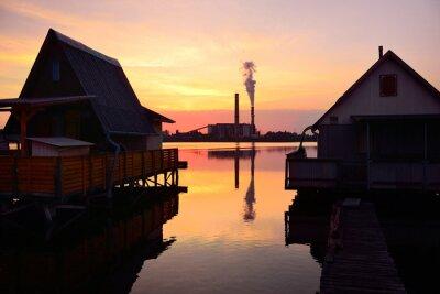 Häuser auf dem Wasser und alten Fabrik mit viel Verschmutzung im Sommer Sonnenuntergang