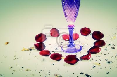 Herz von roten Rosen Blütenblättern und einem Glas