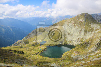 High altitude mountain landscape with lake, stones and sky